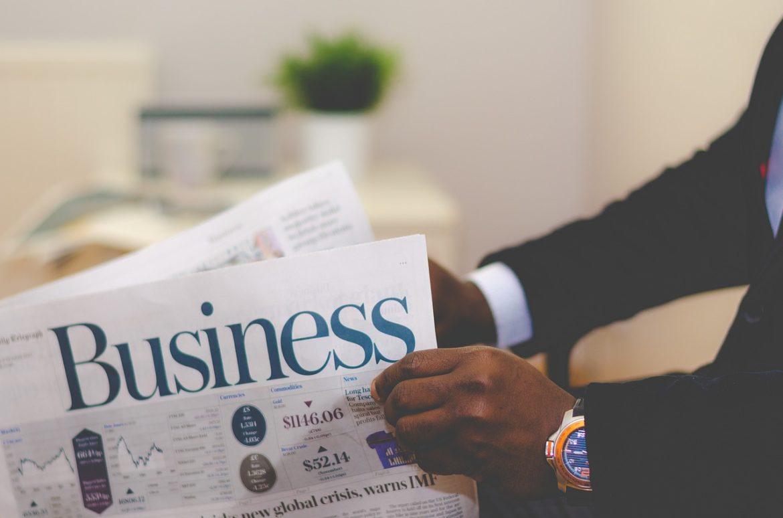 איש עסקים שוקל איפה להשקיע כסף קורא עיתון כלכלי